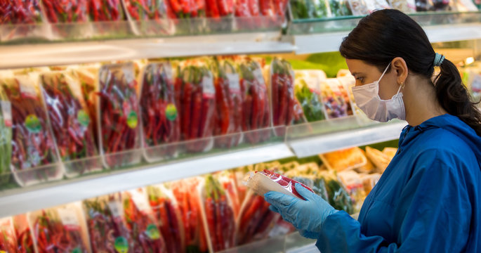 Young woman wears medical mask and protective gloves against coronavirus covid-19 while grocery shopping in supermarket or store- health, safety and pandemic outbreak concept