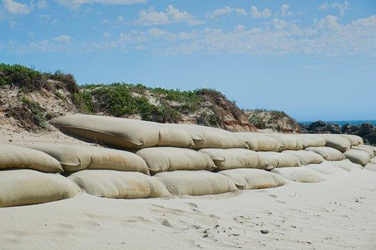 large burlap or hessian sandbags stopping soil erosion on a beach