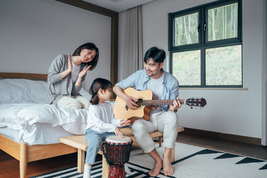 Mom and Dad and daughter sing at home