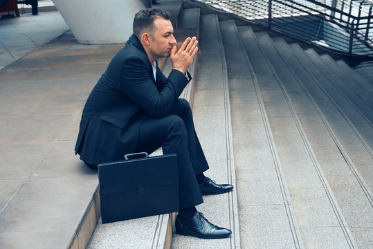 Businessman sit on the stairs and pray for apply job , layoff concept.