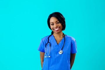 Portrait of a smiling female doctor or nurse wearing blue scrubs uniform and stethoscope and looking to side, isolated on blue background