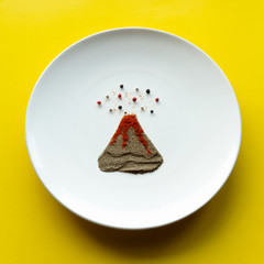 erupting volcano lined with ground pepper and peppercorns.