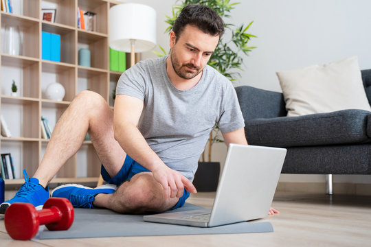 Man doing home work out while watching tutorial on laptop