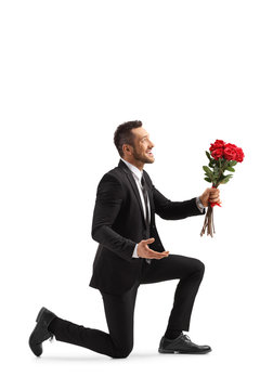 Young handsome man kneeling with a bunch of red roses