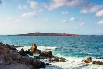 seascape with rocks and cliffs. beautiful scenery in the afternoon light. island in the distance. fluffy clouds on the evening sky. st. Ivan and st. Peter island of bulgaria in the distance