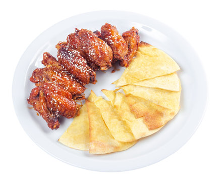 chicken wings in spicy sauce. popular pub dish. beautiful junk food concept. isolated on a white plate.