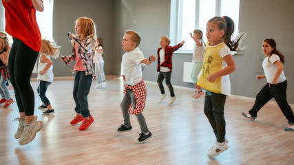 Photo Blinds Dance School Full of energy. Group of little boys and girls dancing while having choreography class in the dance studio. Female dance teacher and children