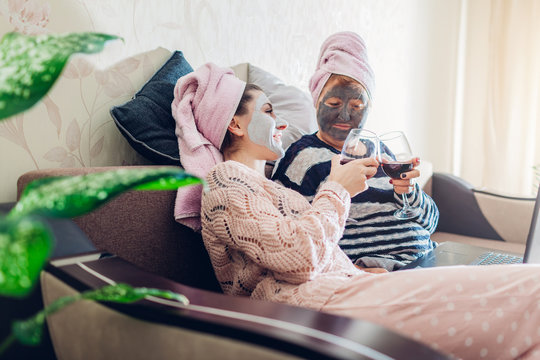 Mother's day. Mother and her adult daughter applied facial masks at home. Women chilling while having wine