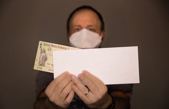 Out of focus caucasian man wearing face mask or N95 respirator holding a United States Treasury check representing economic impart of COVID-19 coronavirus and Government issued stimulus checks.