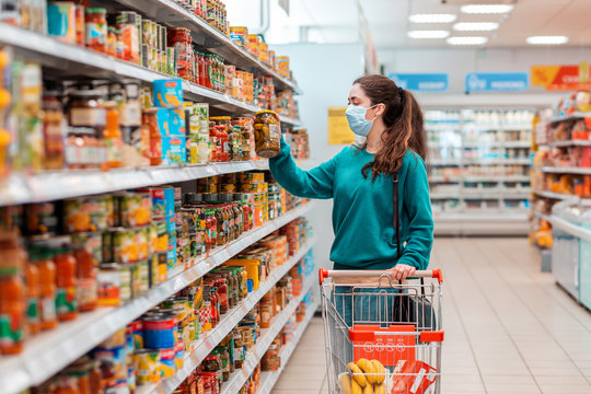 A young pretty Caucasian woman in a medical mask buys a preserved glass jar with vegetable mix at a grocery store. The concept of buying products and the coronovirus pandemic