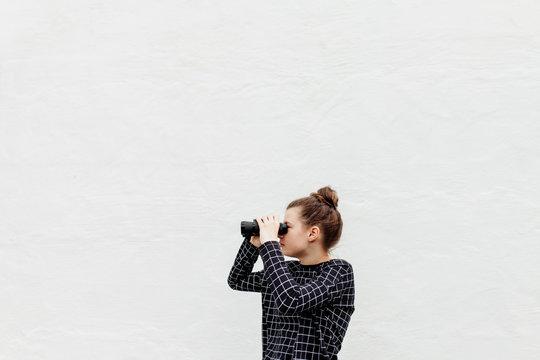 Profile of preteen girl looking through binoculars