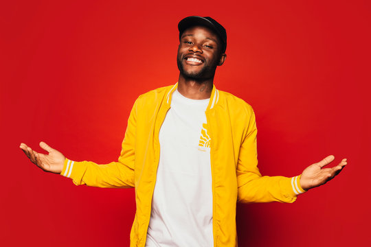 Happy young black man looking at camera over a red background