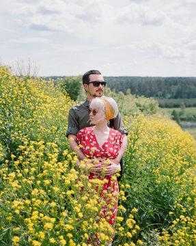 Happy loving couple in a field with summer flowers.