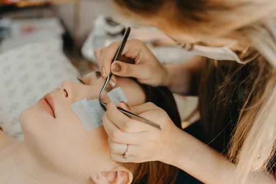 Process of a teenage girl having eyelash extensions put in