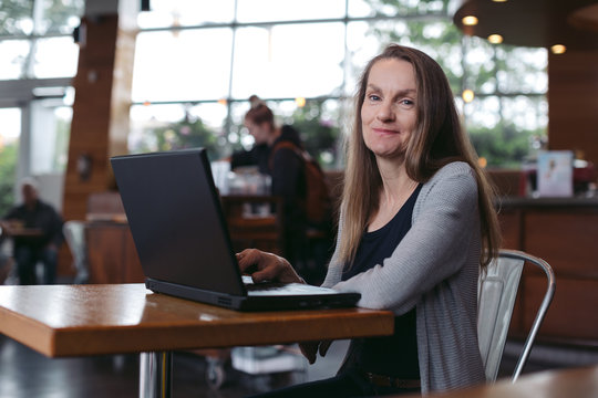 Mature woman working on laptop at coffee shop
