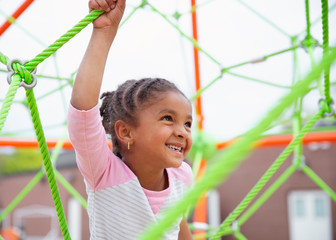Closeup Portrait of a young child with braids in her hair climbing a spider string type structure at a playground