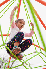 Young child with braids in her hair climbing a spider string type structure at a playground