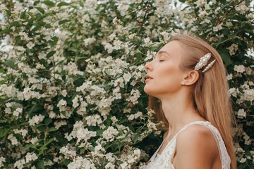 Profile portrait of daydreaming young woman posing by the jasmine