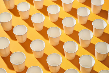 White paper cups of coffee on yellow paper light background.