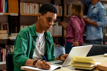 Young male student study in the library using laptop for researching online.