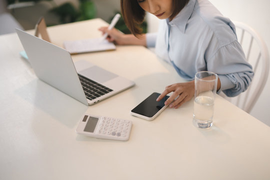 Young asian business woman using cellphone on white desk in office. Business portrait concept.