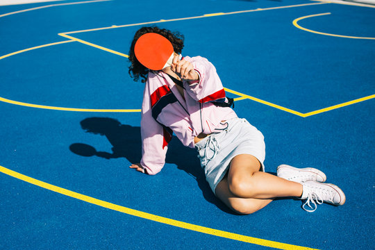 Female Teenager Hiding Face Behind Table Tennis Racket