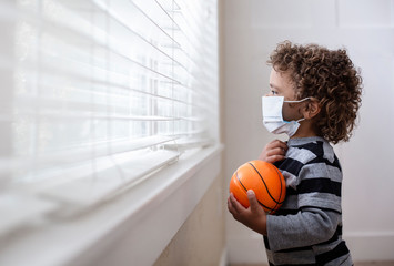 A young boy looking out the window holding his basketball wearing a protective facemark while seeking protection from COVID-19, or the novel coronavirus, by sheltering in place in his home. He is read