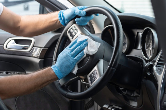 A bearded brown haired man wearing a baseball cap uses alcohol wipes to sterilize the front driver seat, steering wheel, and surrounding areas from any lingering virus strains or germs that are inside