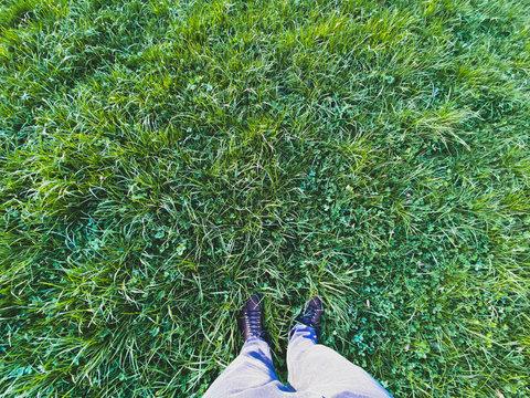 Mann steht im Gras - Bild von oben auf grünes Gras und Füsse