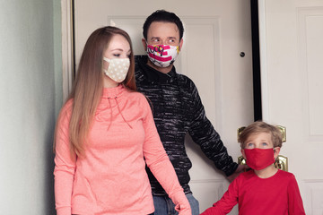 Family exiting their house to go outside wearing face masks. Covering face in public is recommended by CDC in many countries during to Covid-19 coronavirus pandemic. Wall mural
