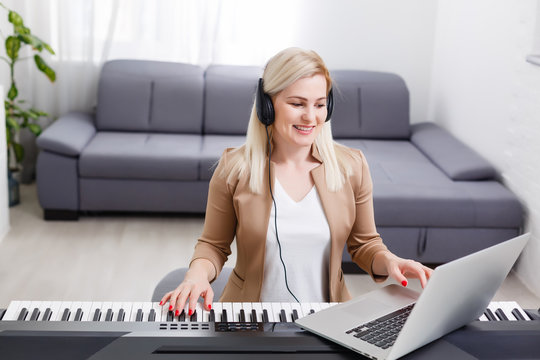 woman musician playing classic digital piano at home during online class at home, social distance during quarantine, self-isolation, online education concept