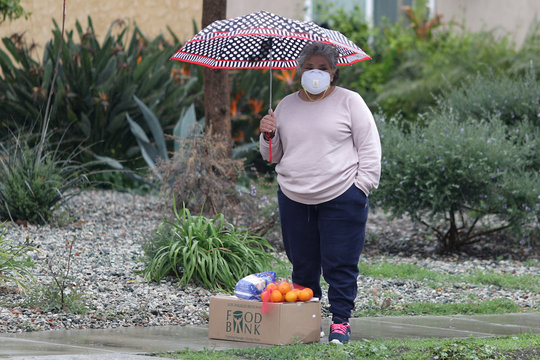 A woman waits in the rain after picking up fresh food at a Los Angeles Regional Food Bank giveaway of 2,000 boxes of groceries, as the spread of the coronavirus disease (COVID-19) continues, in Los Angeles