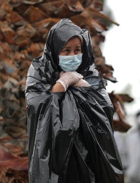 Juana Gomez stands in the rain in a line to pick up fresh food at a Los Angeles Regional Food Bank giveaway in Los Angeles