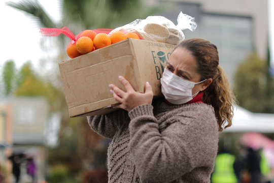 A woman picks up fresh food at a Los Angeles Regional Food Bank giveaway of 2,000 boxes of groceries, as the spread of the coronavirus disease (COVID-19) continues, in Los Angeles
