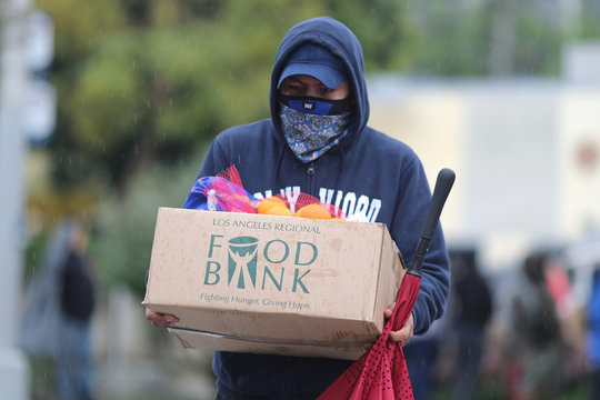 A man carries away fresh food at a Los Angeles Regional Food Bank giveaway of 2,000 boxes of groceries, as the spread of the coronavirus disease (COVID-19) continues, in Los Angeles