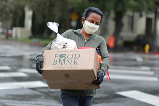 A woman carries away fresh food at a Los Angeles Regional Food Bank giveaway of 2,000 boxes of groceries, as the spread of the coronavirus disease (COVID-19) continues, in Los Angeles