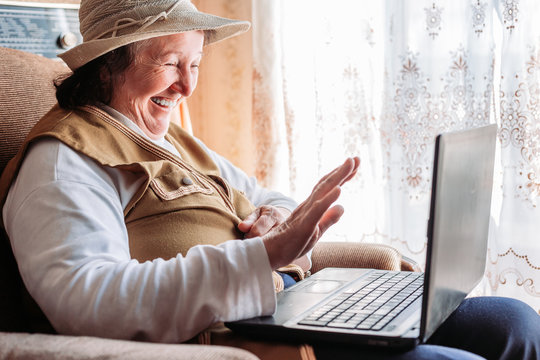 Elderly woman having a video call with her family, smiling and waving.