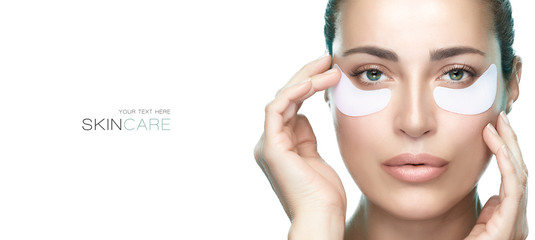 Fototapeta Eyes cosmetic mask. Beautiful young woman with healthy fresh skin using patches under eyes. obraz