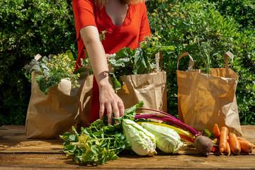 Une jeune femme en robe rouge remplit un des trois sacs de légumes étalés sur une table en bois