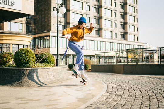 Skateboarding at city. Female, enjoyment. Hipster girl riding skate board. Ride, style. Extreme sport and emotions concept. Alternative lifestyle. Woman skateboarder skateboarding at city