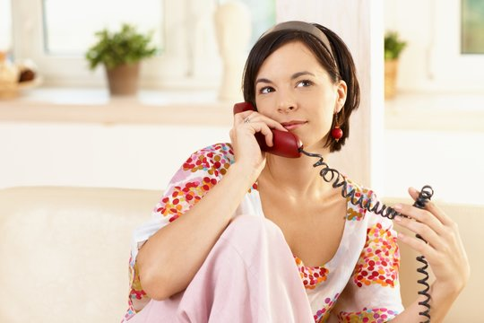 Portrait of happy young woman sitting on sofa at home, talking on landline phone.