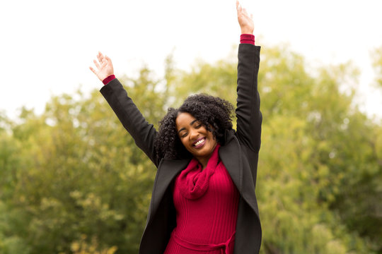 African American woman smiling with open arms.