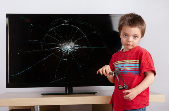 Cute little boy standing in front of a TV with broken screen with his slingshot.