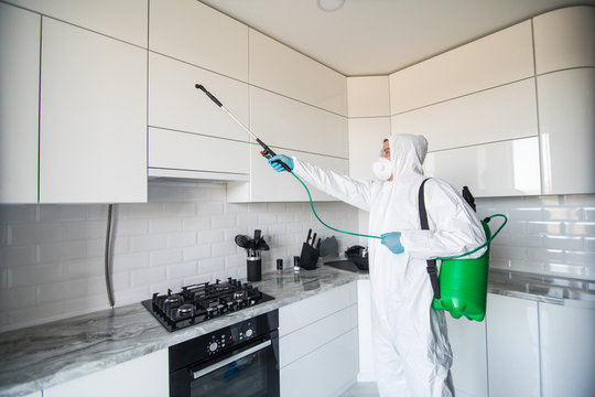 Disinfector in a protective suit conducts disinfection in contaminated area. Professional disinfection against COVID-19, coronavirus. in clothing protecting from chemical poisoning in the kitchen