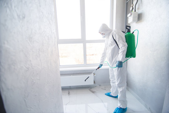 Coronavirus Pandemic. A disinfector in a protective suit and mask sprays disinfectants in house. Protection against COVID-19 disease. Prevention of spreding pneumonia virus with surfaces.