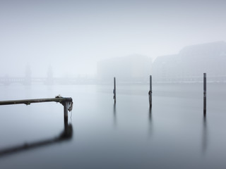Wooden Posts And Jetty Amidst Calm Lake During Foggy Weather