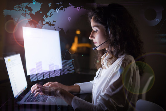 Focused woman in headset and virtual statistic graphics. Side view of young serious call center operator working with laptop computer in dark office. Client service concept
