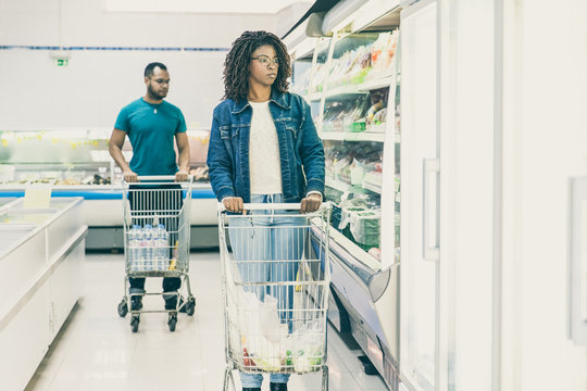 Multiethnic customers walking along isles in grocery store, wheeling carts, choosing product. Buyers shopping in supermarket. Buying fresh food concept