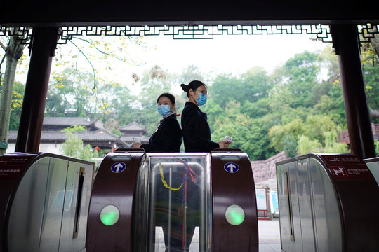 Staff members wearing face masks hold thermometers at an entrance to the Yellow Crane Tower attraction in Wuhan