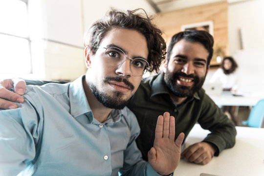 Young entrepreneurs having fun and posing in co-working. Business colleagues in casual working together in contemporary office space. Startup leaders concept